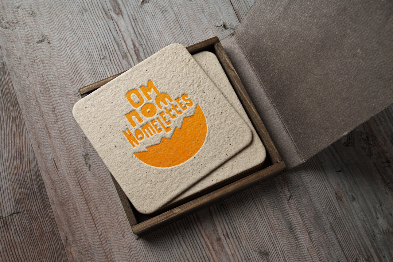 Om Nom Nomelettes logo mockup relief printed on drink coasters